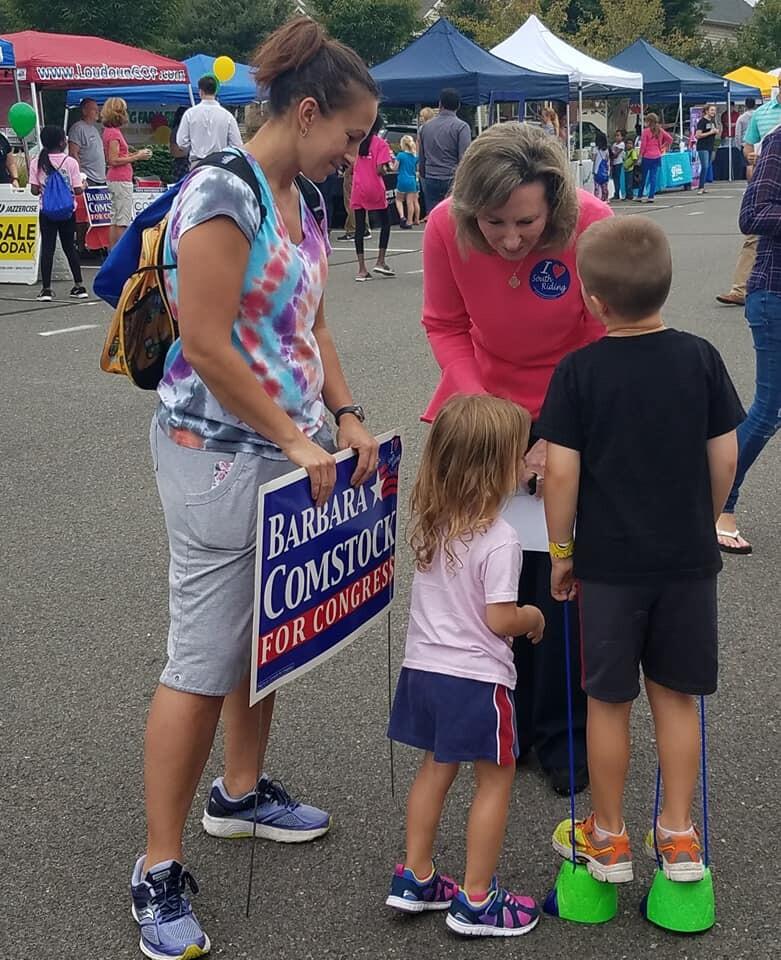当女议员与弗吉尼亚州南骑马的两个孩子谈话时,一名女子(左图)举行了一场竞选标志,赞成罗马的众议员芭芭拉康斯托克(右图)。