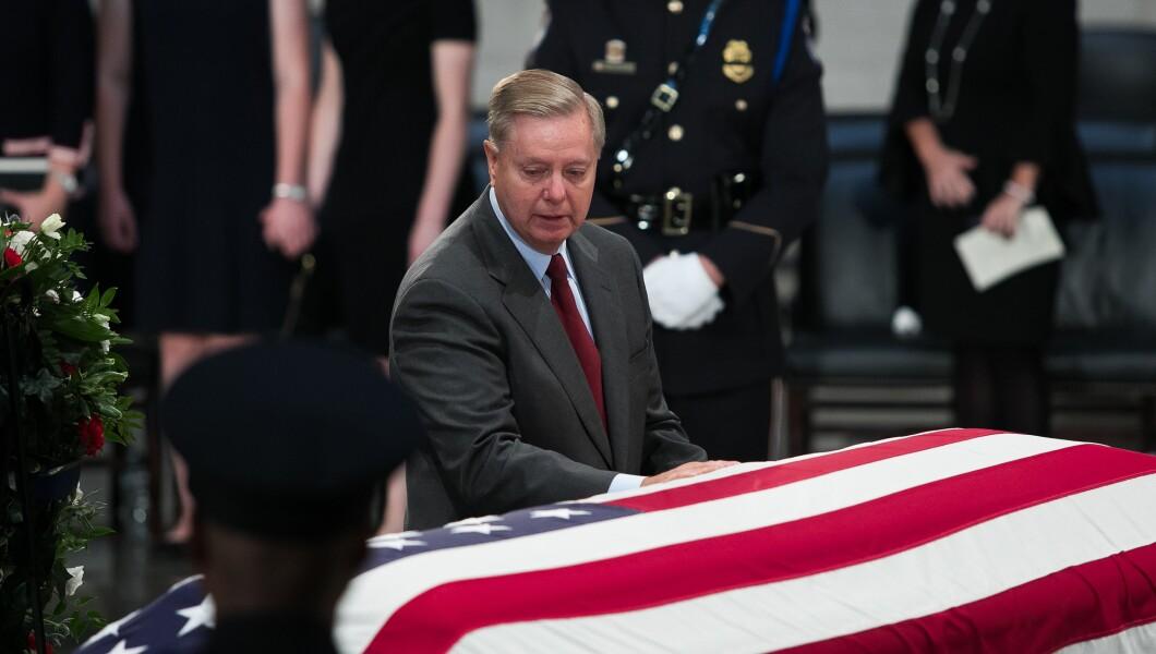 参议员林赛格雷厄姆,R-S.C。,站在国会大厦参议员约翰麦凯恩的旗帜棺材前面。