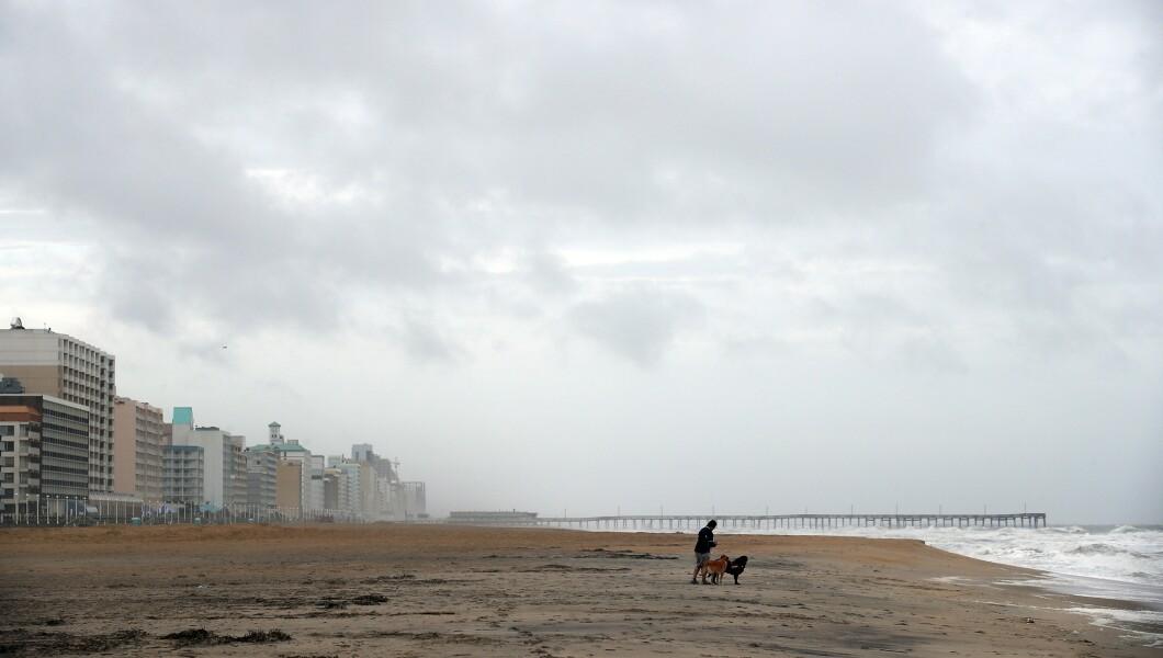 凯莉麦圭尔于2018年9月14日星期五在弗吉尼亚州弗吉尼亚海滩的一个大部分荒凉的海滨沙滩上遛狗杰克和罗克西,感受佛罗伦萨飓风的影响。