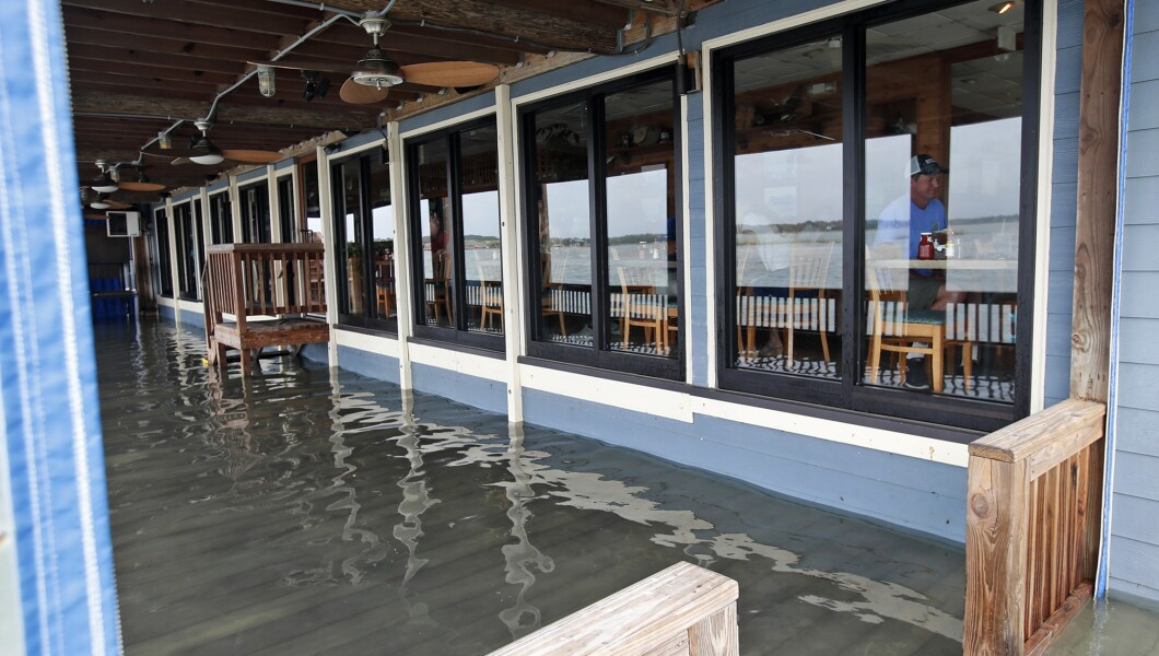来自宾夕法尼亚州Manteo的Sean Hayes和他的家人一起在Bubba的海鲜餐厅吃饭,周五在弗吉尼亚州弗吉尼亚海滩,佛罗伦萨飓风影响了几英寸长的水。