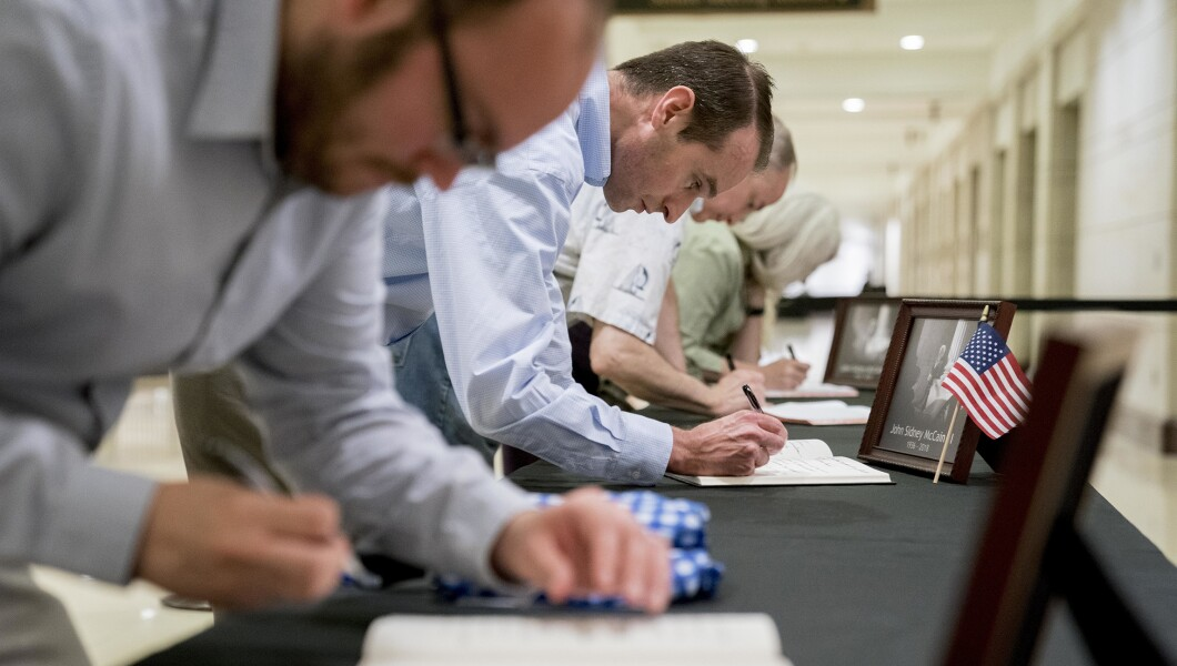 参观者在国会游客中心签署慰问书,参议员约翰麦凯恩,亚利桑那州,位于美国国会大厦圆形大厅,于2018年8月31日星期五,在华盛顿。