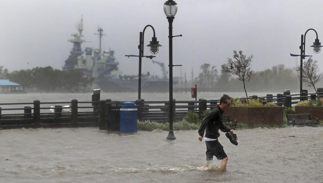 在佛罗伦萨飓风星期五登陆后,一名男子穿过位于北威尔士市中心的一条被水淹没的街道。
