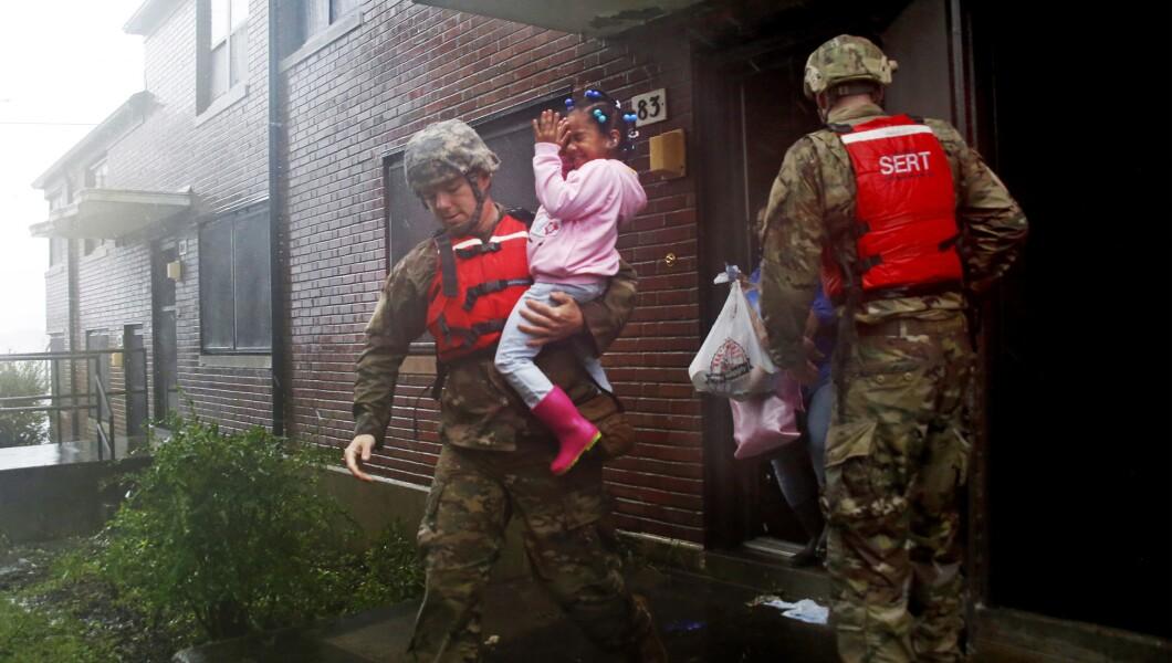 来自北卡罗来纳州国民警卫队1/120营的一支救援队撤离了一个家庭,因为佛罗伦萨飓风上升的洪水威胁他们周五在新伯尔尼的家。