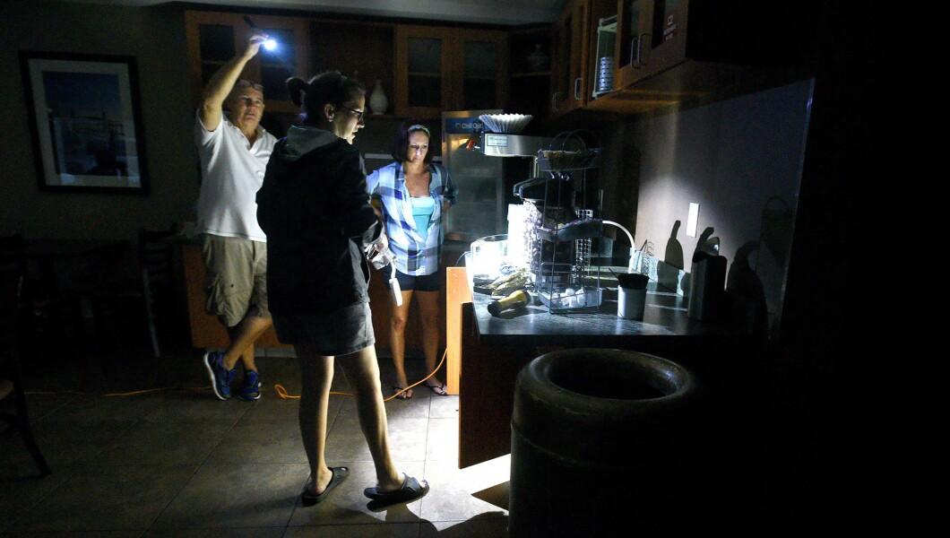 Mitchell Floor左手拿着手电筒,因为Comfort Suites总经理Beth Bratz,中心和员工Dee Branch去周五在威尔明顿的飓风佛罗伦萨肆虐咖啡。该区域在凌晨4点左右失去电力,该设施在发电机上运行小灯,电话充电器和咖啡机。