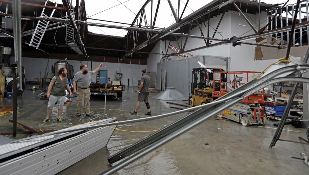 在佛罗伦萨飓风星期五登陆后,Ethan Hall,右,Michael Jenkins,中心和Nash Fralick离开,检查了N.C.的Tidewater Brewing Co.的损坏情况。