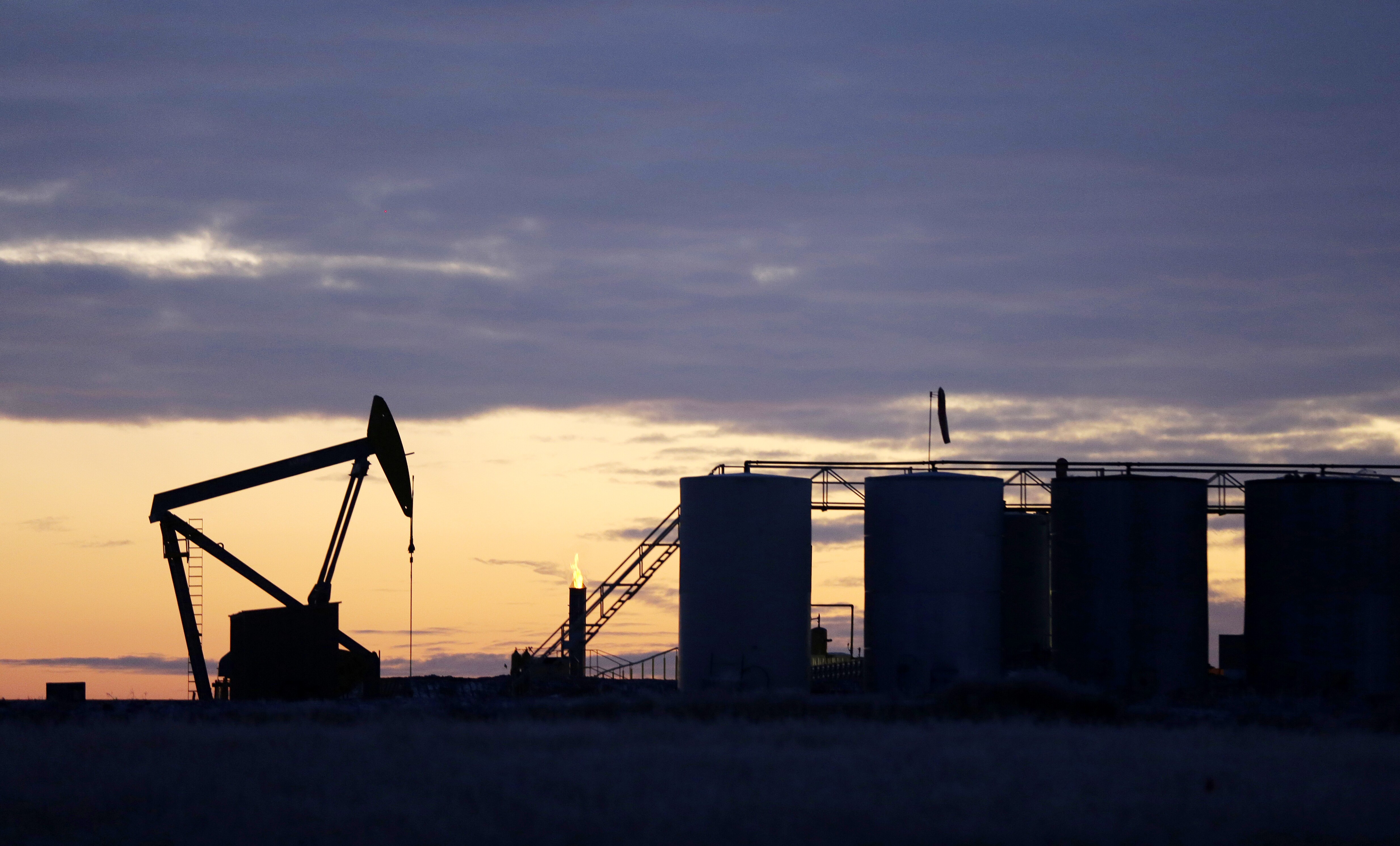 The sun begins to rise behind a pump jack and oil storage tanks near Williston, N.D.