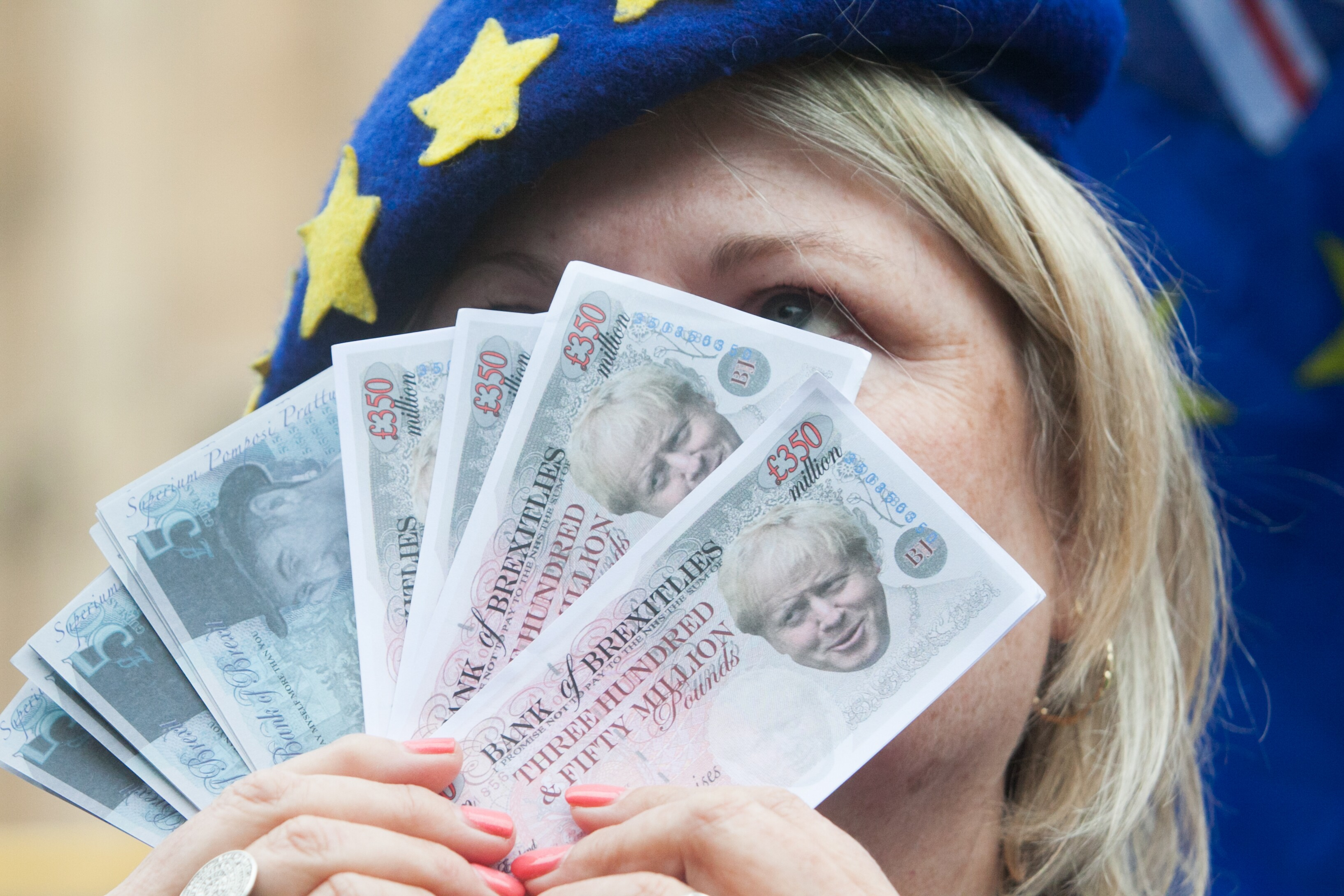 A Pro EU protester holds fake bank notes of Boris Johnson and Jacob Rees Mogg outside Parliament in June 2018 Barcroft Media/Barcroft Media via Getty Images