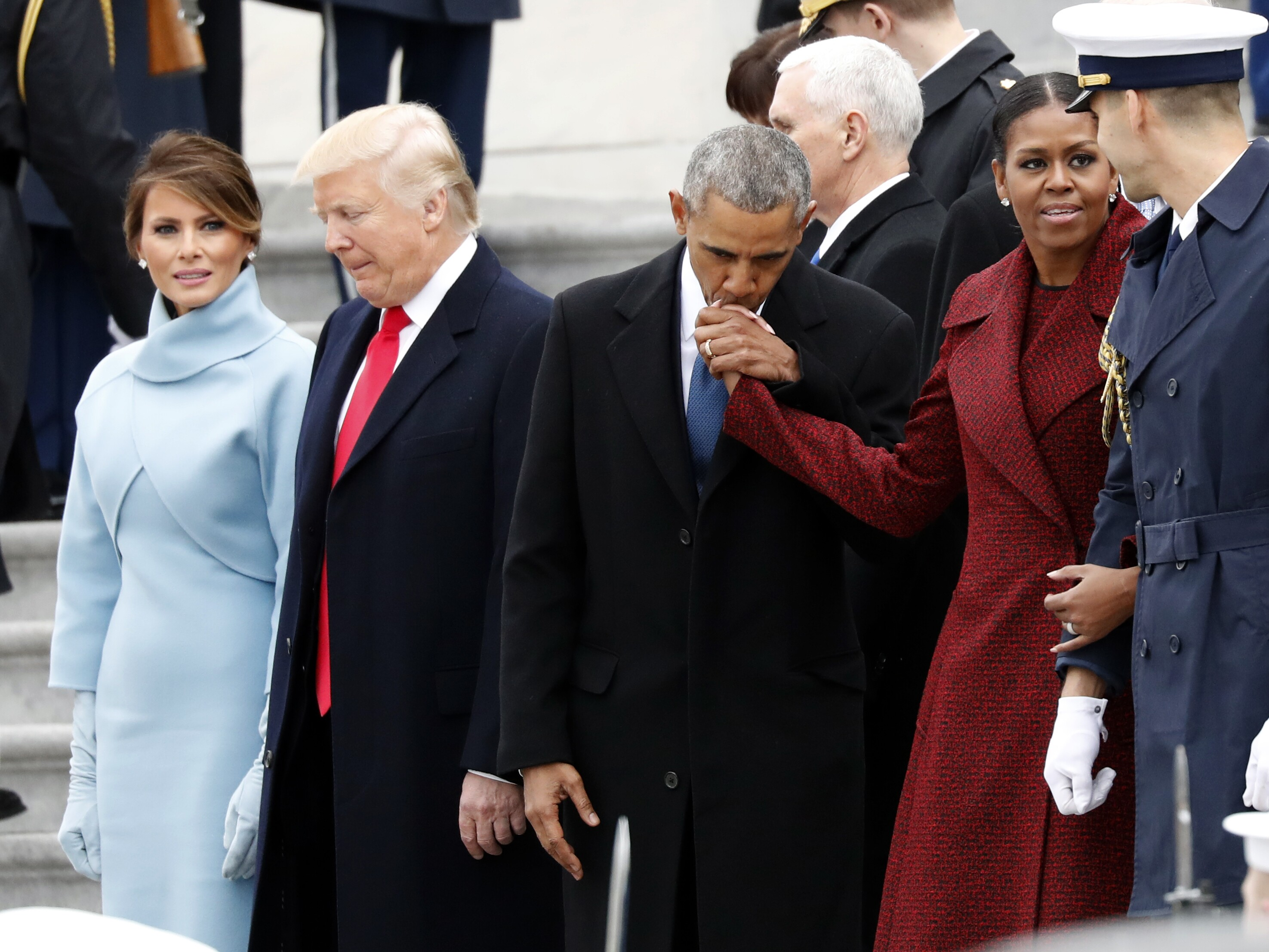 First Lady Melania Trump Stands With President Donald As Former Barack Obama Kisses The Hand Of His Wife Michelle During A Departure