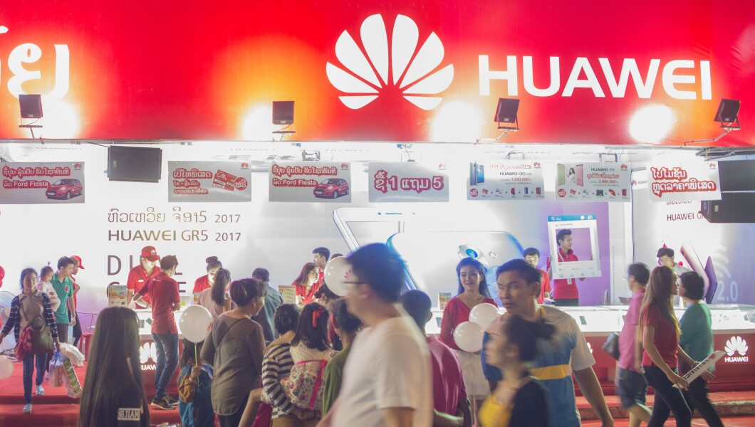Passersby walking by a logo of Chinese technology company Huawei.