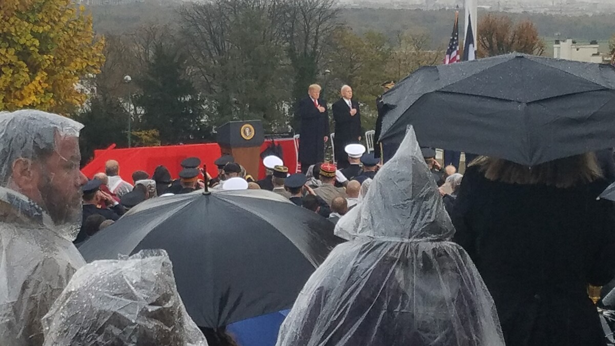 Trump speaks at military cemetery without umbrella in soaking rain
