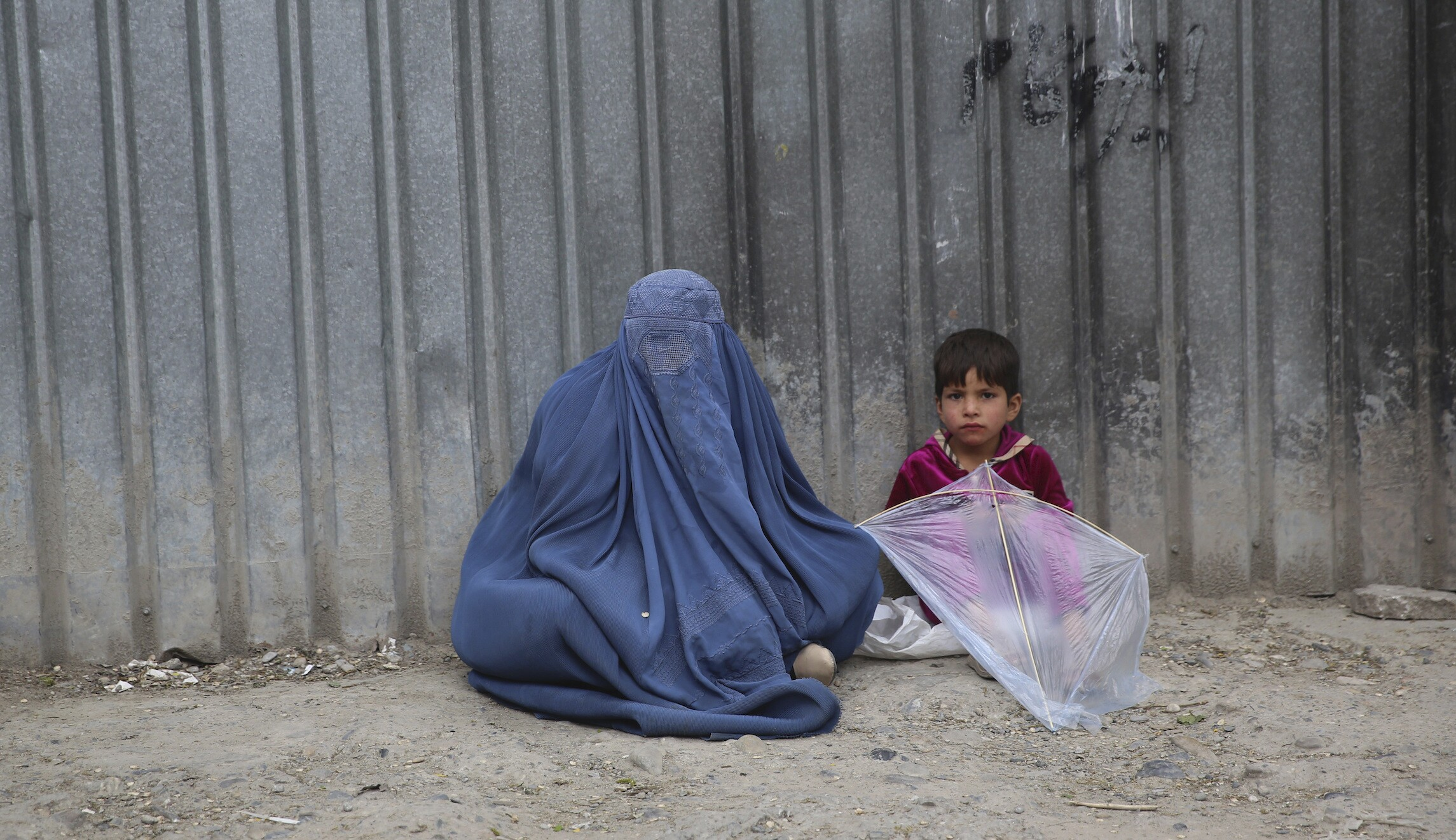 In this May 2, 2020 file photo, a woman waits to receive alms with her daughter during the Muslim fasting month of Ramadan, in Kabul, Afghanistan.