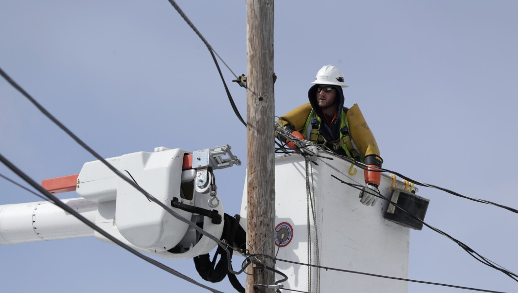 A utility worker tries to do his job near a power line.