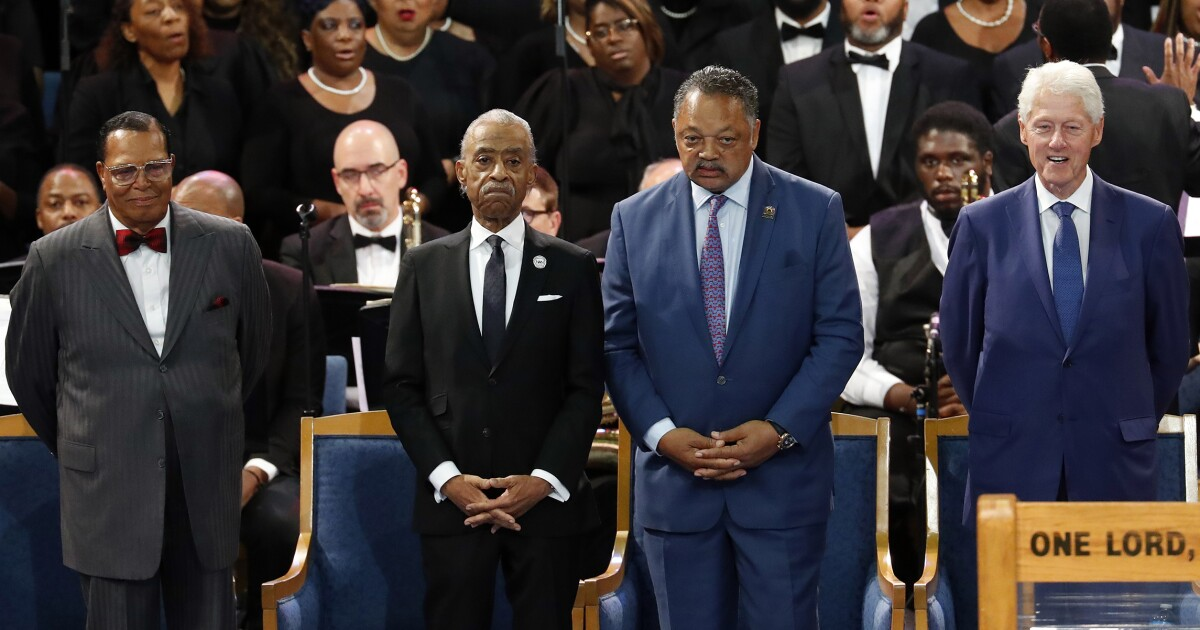 Bill Clinton sits with Nation of Islam leader Louis Farrakhan at Aretha Franklin...