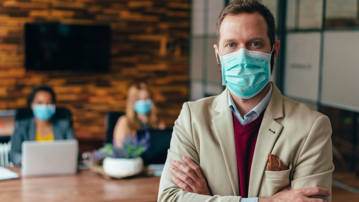 Businesspeople working with face masks in the office during COVID-19 pandemic