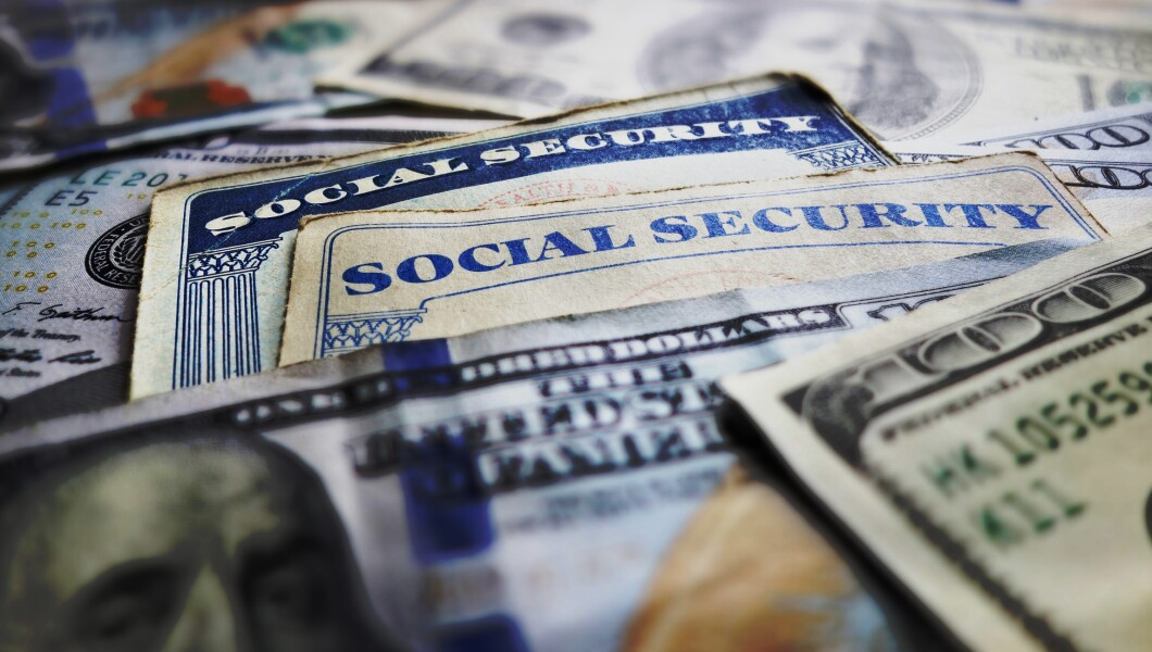 A stock photo is shown with old Social Security cards and $100 bills.