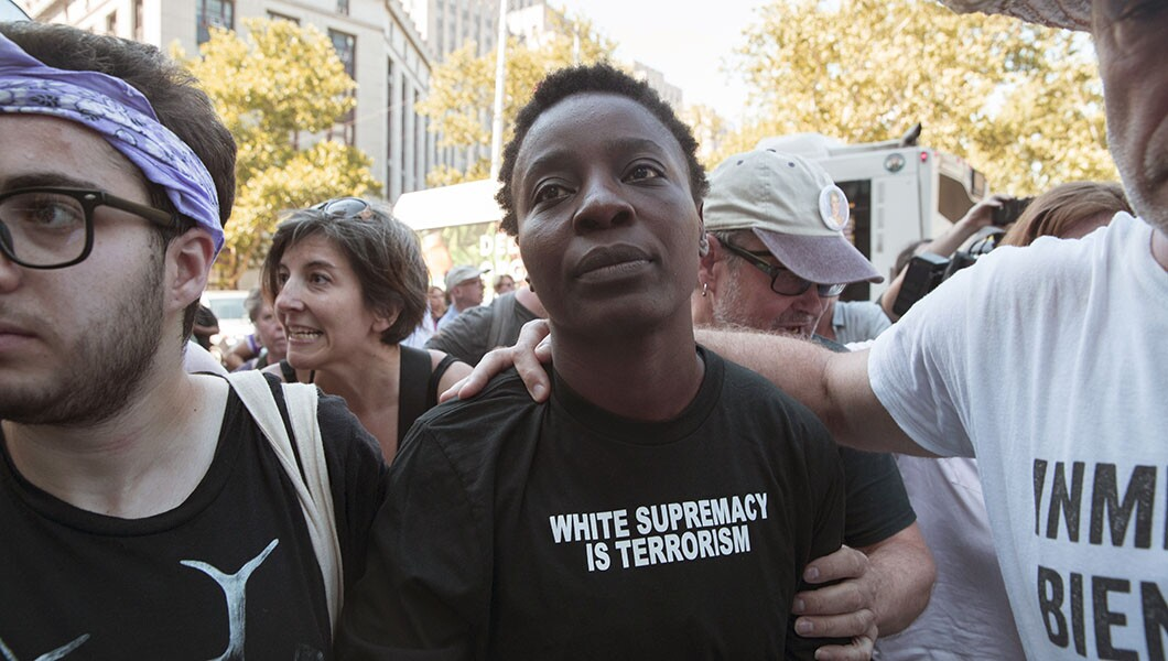 Therese Okoumou surrounded by supporters as she leaves Federal court, Thursday.