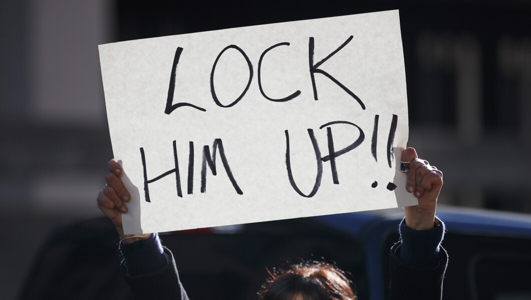 "A woman holds a sign that reads ""Lock Him Up!!"" outside federal court in D.C."