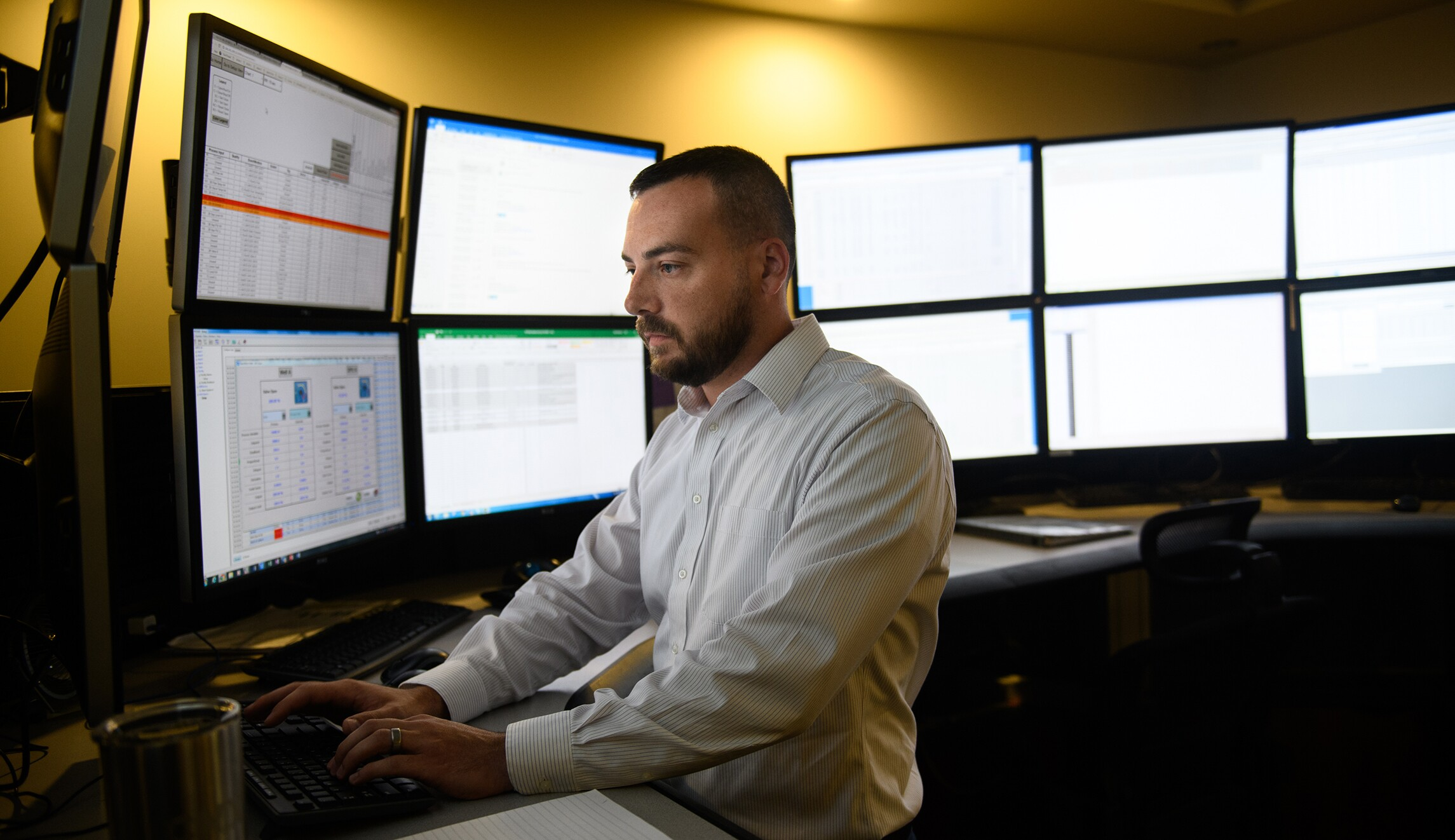 Mike May, 33, of Oakdale, Pa., works in the control room of CNX Resources Corporation on July 30 at their headquarters in Cannonsburg, Pa. The control room is able to monitor and adjust well sites throughout several states.