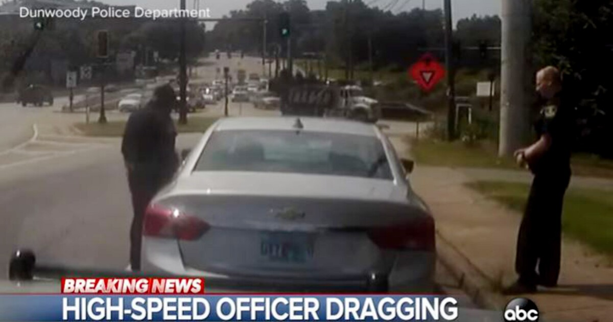 WATCH: Police officer dragged onto freeway as he dangles