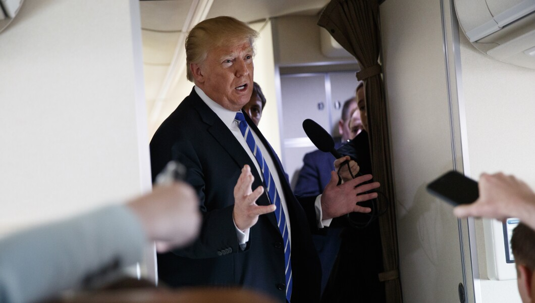 President Trump talks with reporters aboard Air Force One on a flight to Andrews Air Force Base