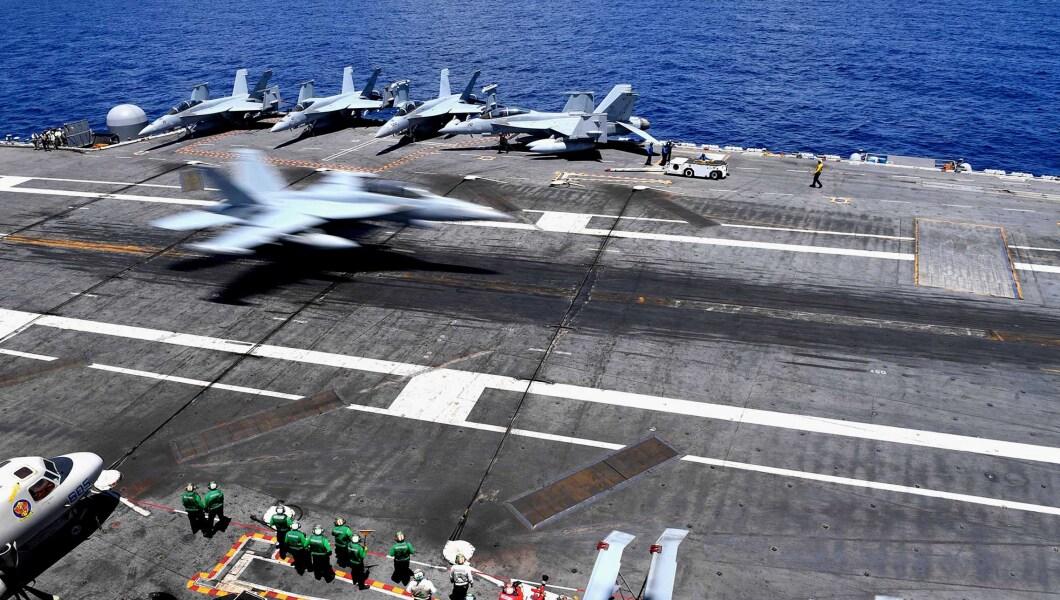 An F/A-18 Super Hornet lands on the flight deck aboard the Nimitz-class aircraft carrier USS Abraham Lincoln.