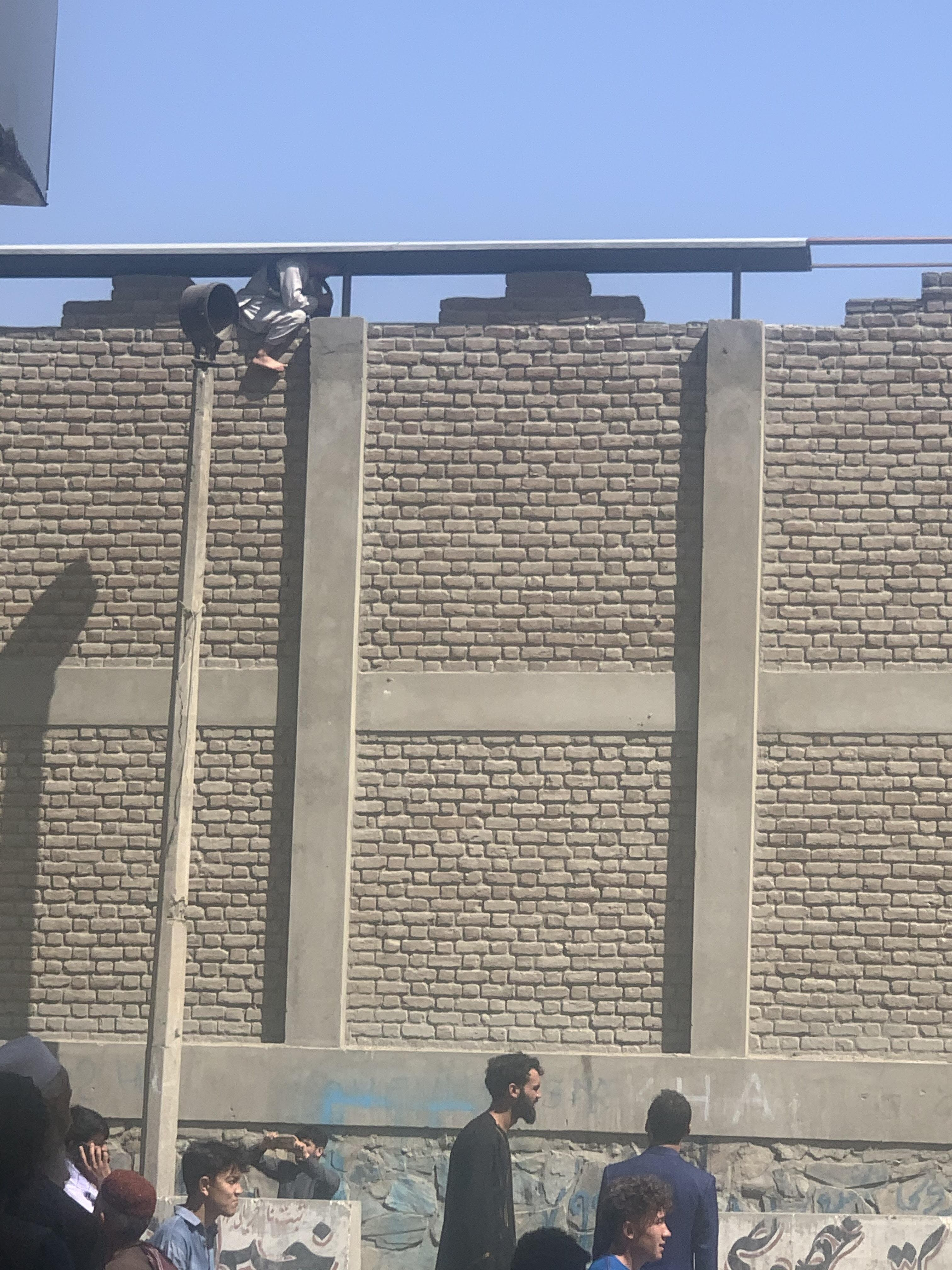 Afghan sitting on airport wall