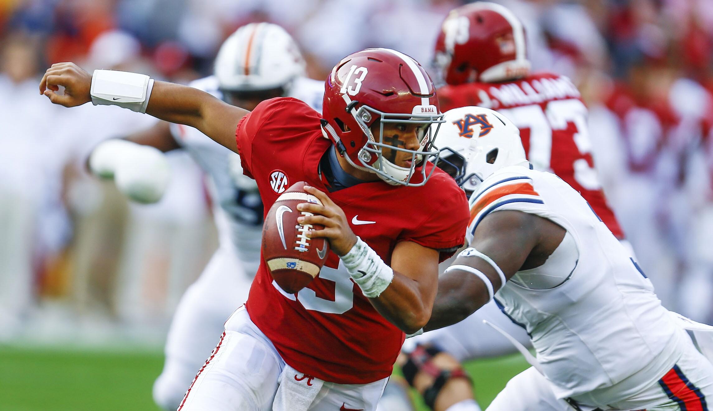 e6c3f8e23a7 Alabama quarterback Tua Tagovailoa (13) escapes pressure from Auburn  defensive lineman Marlon Davidson (