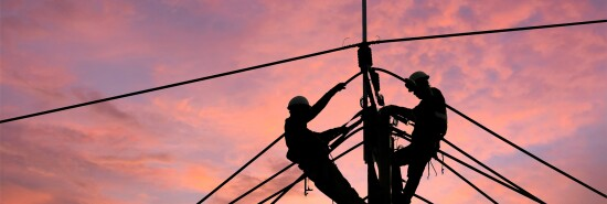 Electrician worker climbing electric power pole to repair the damaged power cable line problems after the storm. Power line support,Technology maintenance and development industry concept