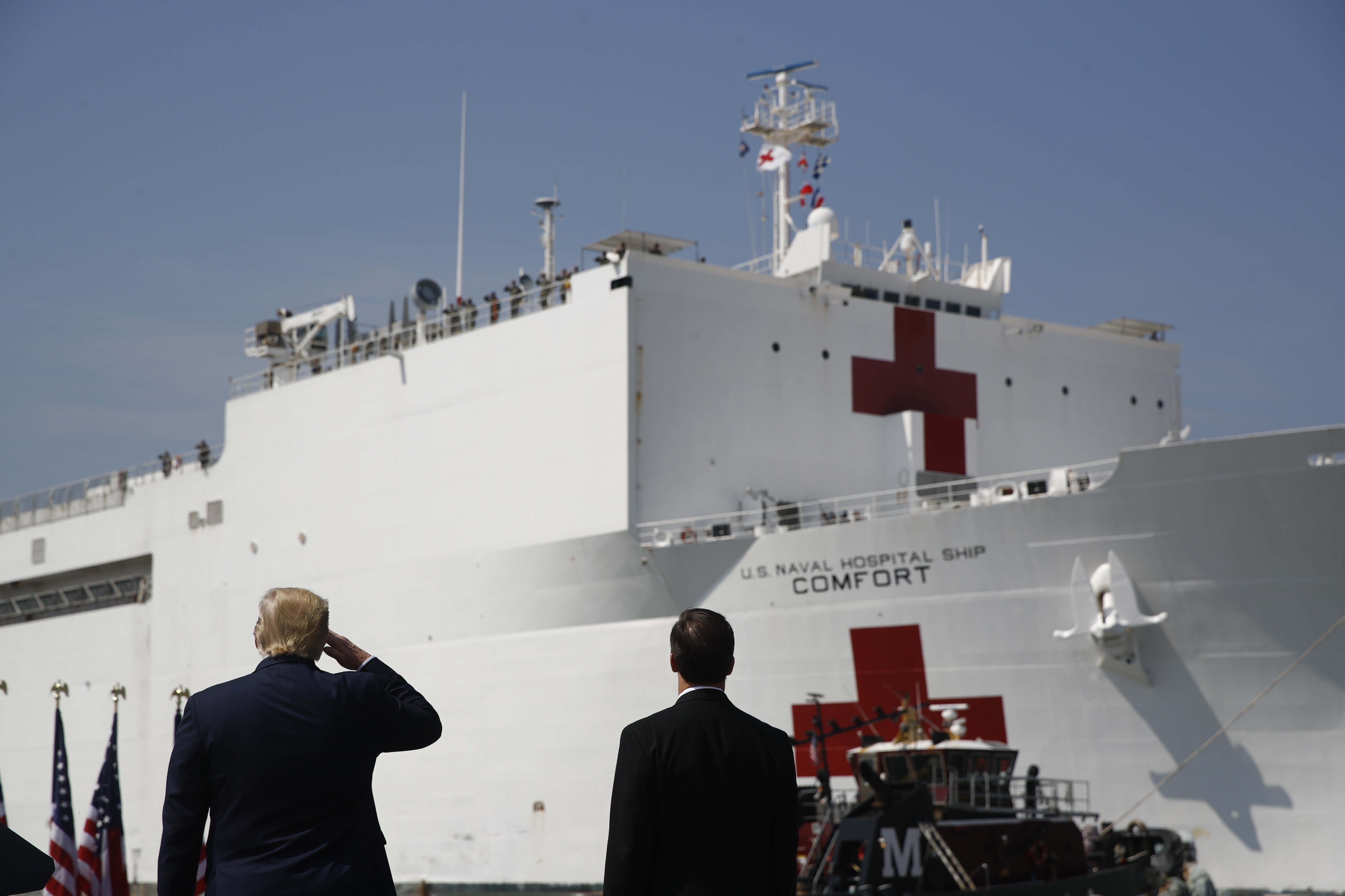 President Trump salutes as the U.S. Navy hospital ship USNS Comfort pulls away from the pier at Naval Station Norfolk in Norfolk, Virginia, on Saturday.